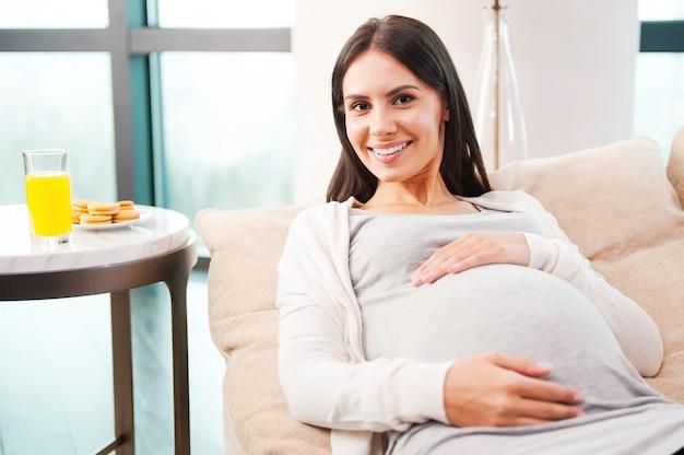Demnächst... schöne junge schwangere frau, die ihren bauch berührt und lächelt