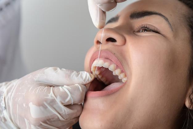 Demonstration der verwendung von dentaldraht. lehrender patient des zahnarztes, wie man zahnseide benutzt.