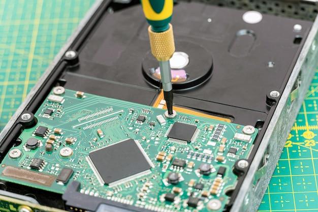 Demontageprozess der festplatte mit schraubendreher bei der informationswiederherstellung, reparatur des festplattenservice