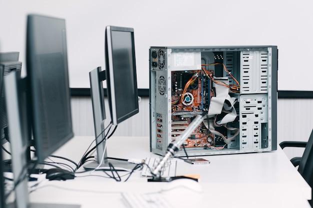 Demontierte computereinheit auf tisch mit monitoren. elektronische reparaturwerkstatt, werkstatt, industrie, renovierungskonzept
