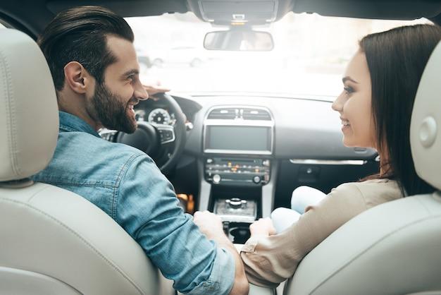 Den augenblick genießen. rückansicht eines jungen paares, das auf den beifahrersitzen sitzt und sich ansieht, während ein gutaussehender mann ein auto fährt?