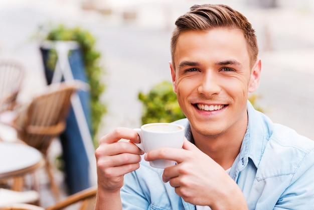 Den besten kaffee der stadt genießen. fröhlicher junger mann, der kaffee trinkt und lächelt, während er im straßencafé sitzt?