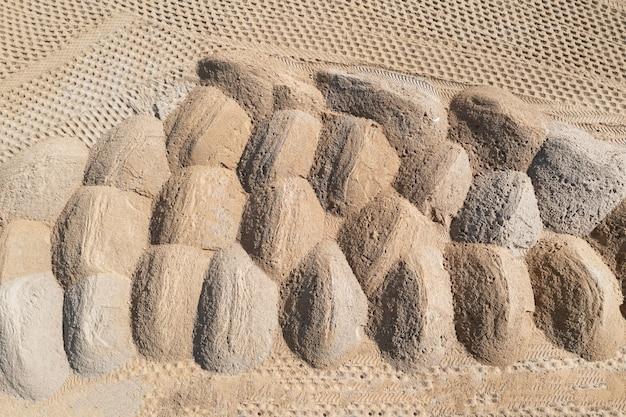 Den boden nivellieren. leere baustelle eines wohngebiets mit einem sandhaufen. luftaufnahmen