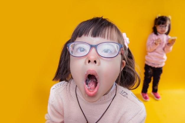 Den mund voll haben. dunkelhaariges mädchen mit down-syndrom, das den mund öffnet und darin essensreste zeigt