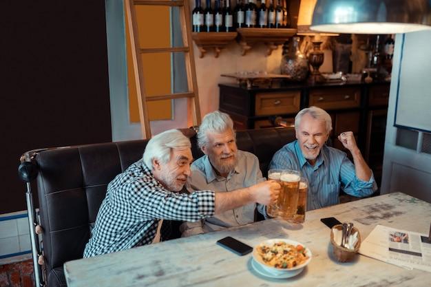 Den sieg feiern. drei glückliche rentner feiern den sieg der lieblingsfußballmannschaft