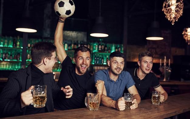 Den sieg feiern. drei sportfans in einer bar beim fußball schauen mit bier in der hand