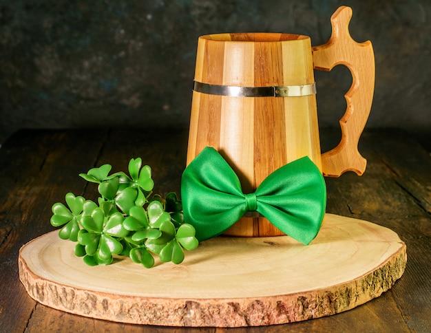 Den st. patrick day feiern. holzkrug grünes bier, grüne fliege und ein zweig kleeblatt auf naturholz