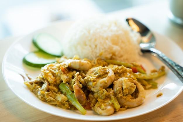 Den tintenfisch mit curry auf dem gekochten reis anbraten