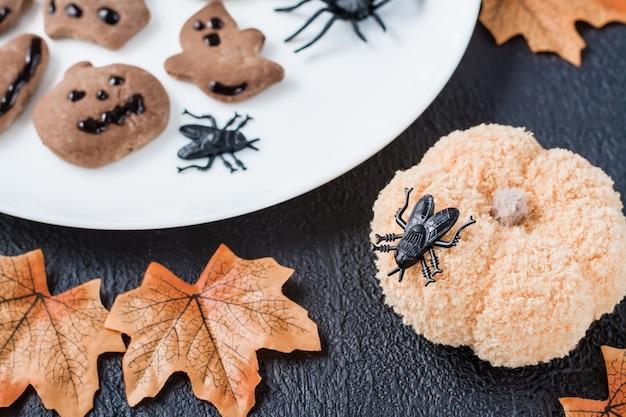 Den tisch mit handarbeiten für halloween dekorieren. schwarze fliege auf einem gestrickten kürbis vor dem hintergrund von lebkuchen auf einem teller. traditionelle feier