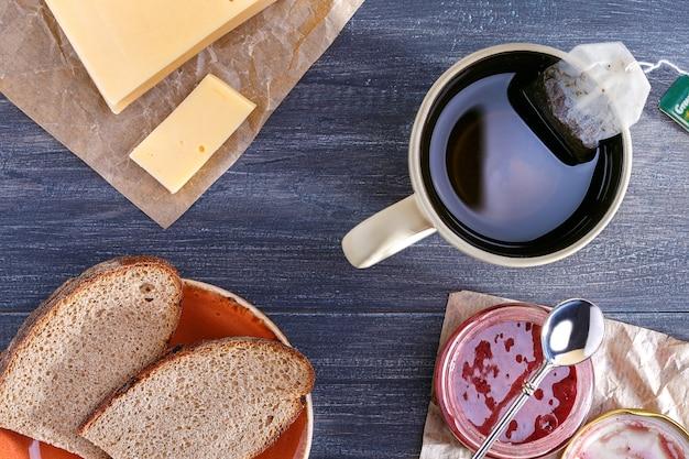 Den tisch zum frühstück vorbereiten. tasse tee und brot mit käse, glas marmelade.