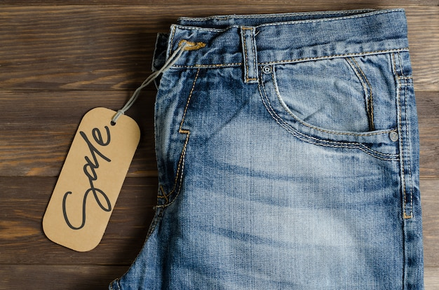 Denim. blue jeans auf braunem hölzernem. verkauf, handschriftliche inschrift auf einem papieretikett.