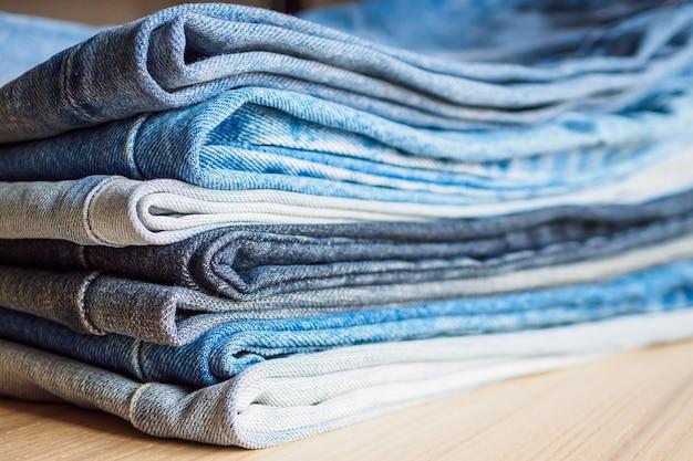 Denim blue jeans stapel auf holztisch hintergrund
