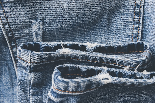 Denim blue jeans textur mit kratzern und löchern. abstrakter hintergrund.