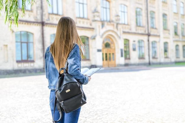 Denim-jeans-freizeitkleidung beginnen lehrerjob-leute-karriere-sommer-konzept. zurück hinter der hinteren nahaufnahme fotoporträt eines selbstbewussten gestressten mädchens, das ein buchtagebuch in den händen hält, verschwommener hintergrund