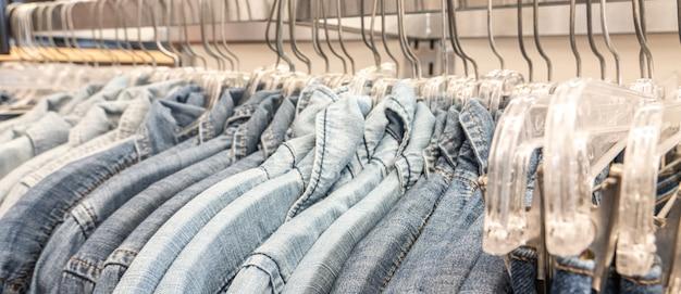 Denim-jeanshemden der männlichen männer sortiert auf kleiderbügeln auf einer shopgarderoben-wandschrankschiene