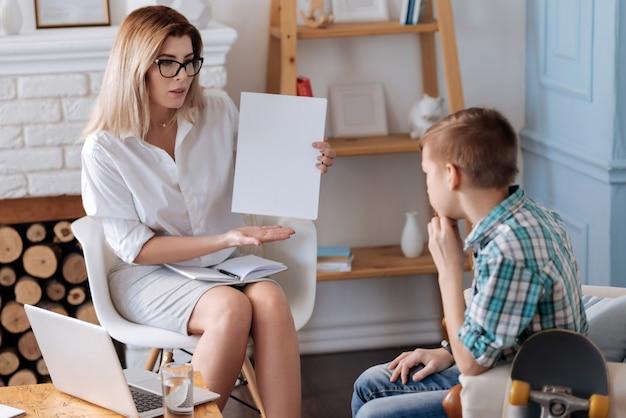 Denk darüber nach. ernsthafte psychologin, die notizbuch auf ihren knien hält und weißes blatt papier in der linken hand hält, während sie auf teenager schaut