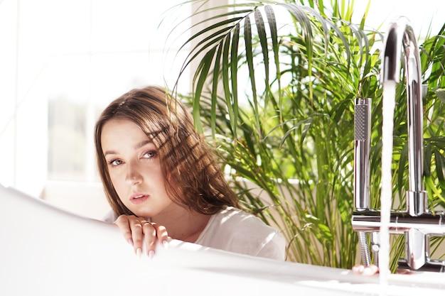 Denk positiv. mädchen in einem hellen badezimmer mit einer grünen pflanze. eine glückliche frau wartet, bis die badewanne mit wasser gefüllt ist
