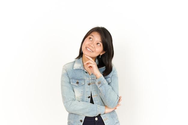 Denken an schöne asiatische frau mit jeansjacke und schwarzem hemd isoliert auf weißem hintergrund