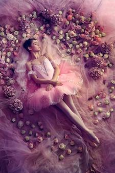 Denken an warm. blick von oben auf die schöne junge frau im rosa ballett-ballettröckchen, umgeben von blumen. frühlingsstimmung und zärtlichkeit im korallenlicht. kunst foto. konzept des frühlings, der blüte und des erwachens der natur.
