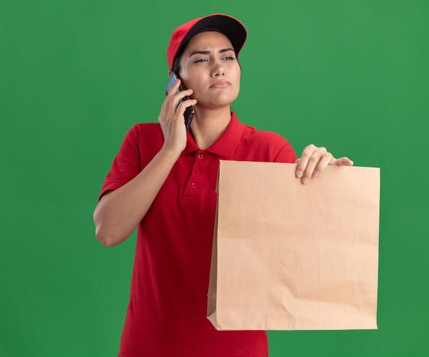 Denken, das das junge liefermädchen der seite betrachtet, das uniform und kappe hält, die papiernahrungsmittelpaket hält und am telefon lokalisiert auf grüner wand spricht