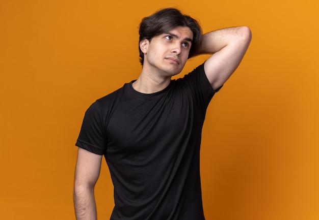 Denken, das den jungen gutaussehenden mann der seite betrachtet, der das schwarze t-shirt trägt, das hand hinter kopf lokalisiert auf orange wand setzt