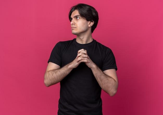 Denken, das den jungen gutaussehenden mann der seite betrachtet, der schwarze t-shirt hält, die hände zusammenhalten, die auf rosa wand lokalisiert werden