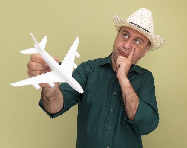 Denken, das mann der seite mittleren alters betrachtet, der grünes t-shirt und hut hält spielzeugflugzeug, das hand auf wange lokalisiert auf olivgrüner wand hält