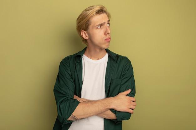 Denken, das seitlichen jungen blonden kerl betrachtet, der grünes t-shirt trägt, das hände kreuzt