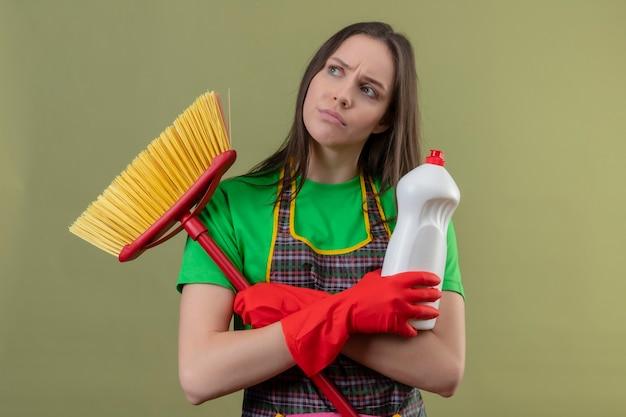 Denken, dass das reinigen des jungen mädchens das tragen der uniform in den roten handschuhen hält, die mopp mit dem reinigungsmittel halten, das hände auf isolierter grüner wand kreuzt
