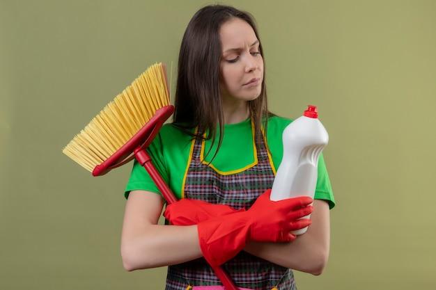 Denken, dass das reinigen des jungen mädchens, das uniform in den roten handschuhen hält, mopp hält, der reinigungsmittel auf ihrer hand betrachtet und hände auf isolierter grüner wand kreuzt