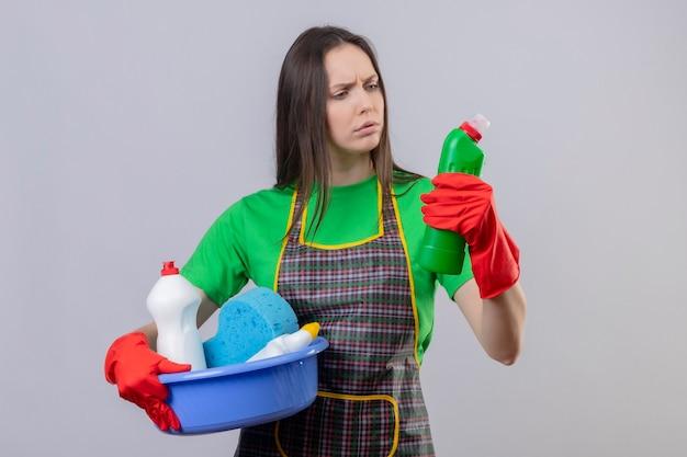 Denken, dass das reinigen des jungen mädchens uniform in roten handschuhen hält, die reinigungswerkzeuge halten und reinigungsmittel auf ihrer hand auf isolierter weißer wand suchen