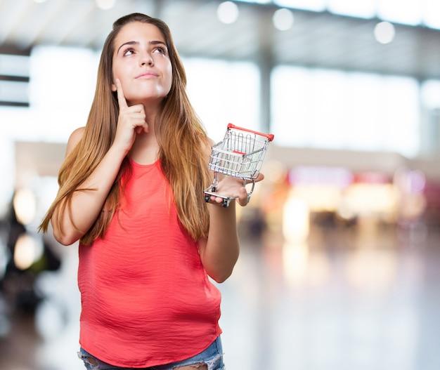 Denken der jungen frau und einen einkaufswagen halten