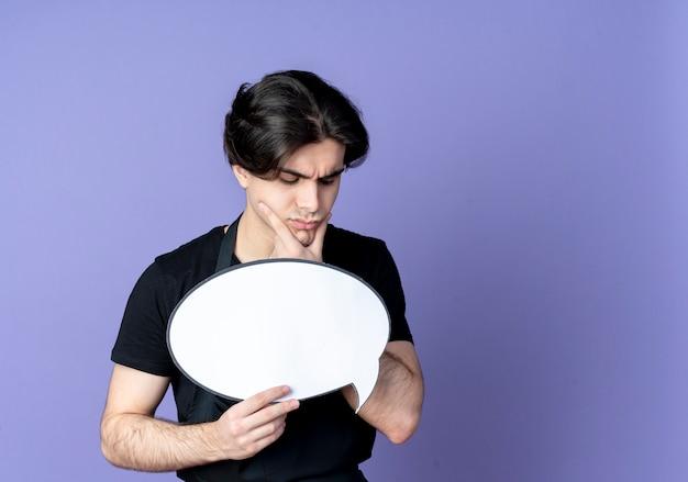 Denken junger hübscher männlicher friseur in der uniform, die chatblase hält und auf blau lokalisiert mit kopienraum betrachtet