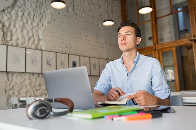 Denken junger schöner mann, der denkt, notizen in notizbuch schreibt