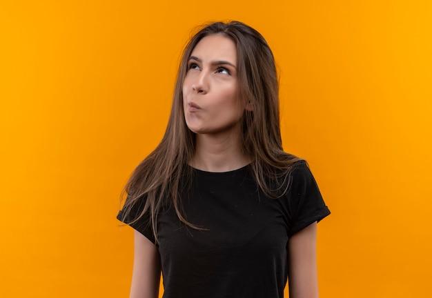 Denken junges kaukasisches mädchen, das schwarzes t-shirt trägt, das seite auf lokalisierter orange wand betrachtet