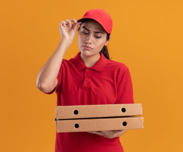 Denken junges liefermädchen, das uniform und kappe hält und pizzakästen hält, die kappe lokalisiert auf orange wand halten