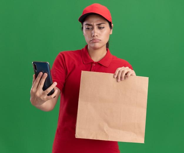 Denken junges liefermädchen, das uniform und kappe trägt, die papiernahrungsmittelpaket hält und telefon in ihrer hand lokalisiert auf grüner wand betrachtet
