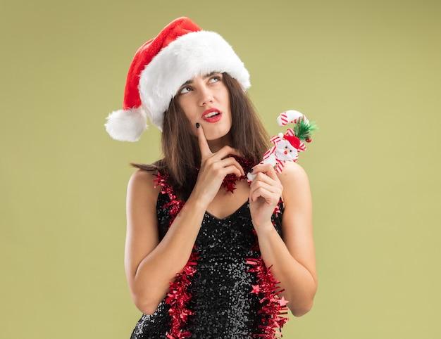 Denken, junges, schönes mädchen mit weihnachtsmütze mit girlande am hals, das weihnachtsspielzeug hält, das den finger auf die wange legt, isoliert auf olivgrünem hintergrund