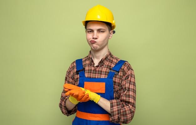 Denken mit den händen zusammen junger männlicher baumeister, der uniform mit handschuhen trägt