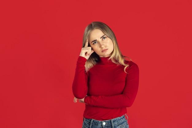 Denken. monochromes porträt der jungen kaukasischen blonden frau lokalisiert auf roter studiowand.