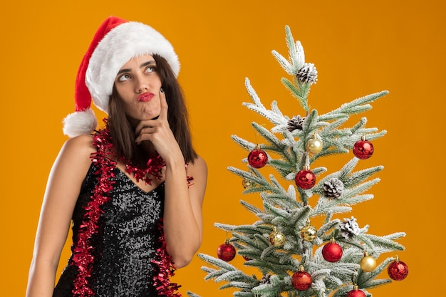 Denken nachschlagen junges schönes mädchen, das weihnachtsmütze mit girlande auf hals steht, der nahe weihnachtsbaum steht, der finger auf wange lokalisiert auf orange hintergrund setzt