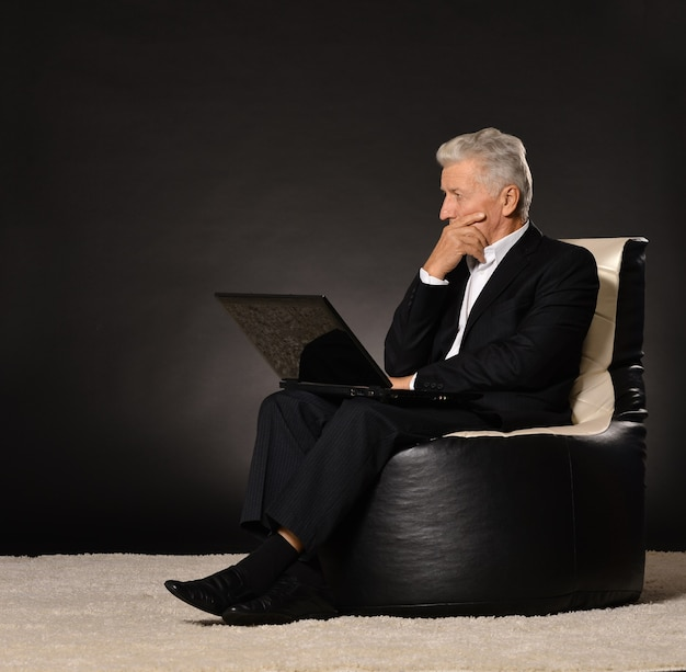 Denken reifer geschäftsmann sitzt im stuhl auf schwarzem hintergrund mit einem laptop