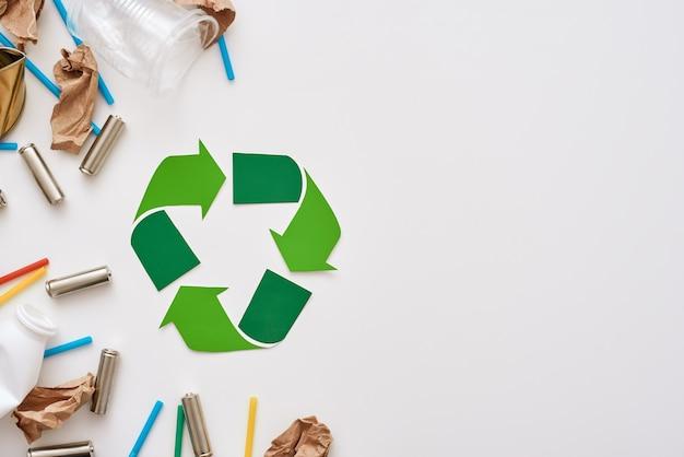 Denken sie an ökologie. zerknittertes papier, plastik und batterien liegen links neben dem recycling-symbol. verschiedene arten von müll unsortiert