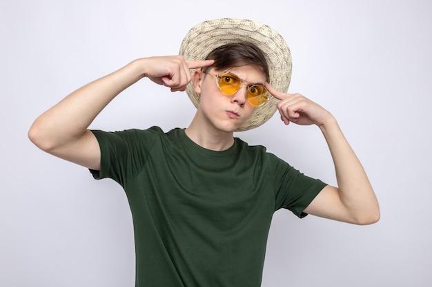Denken sie daran, die finger auf die schläfen zu legen, einen jungen, gutaussehenden kerl mit brille mit hut
