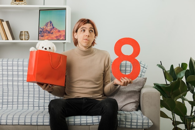 Denken sie nach einem hübschen kerl am glücklichen frauentag, der die nummer acht mit geschenktüte auf dem sofa im wohnzimmer hält