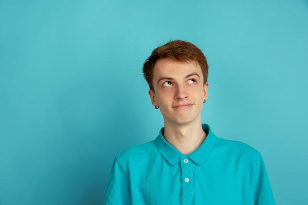 Denken, träumen. das moderne porträt des kaukasischen jungen mannes lokalisiert auf blauer wand, monochrom. schönes männliches model. konzept der menschlichen emotionen, gesichtsausdruck, verkauf, anzeige, trendy.