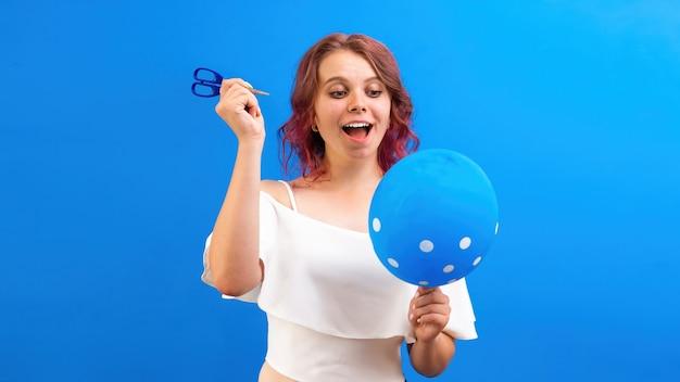 Denken überrascht kaukasische frau mit einem ballon und einer schere