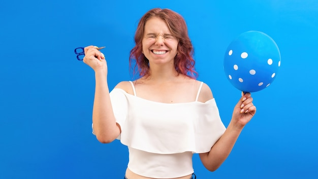 Denken überraschte kaukasische frau mit geschlossenen augen mit einem ballon und einer schere