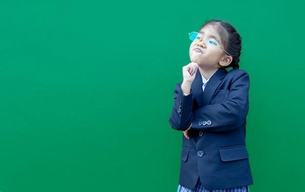 Denkende asiatische schulkinder mit formeller geschäftsuniform auf grünem hintergrund