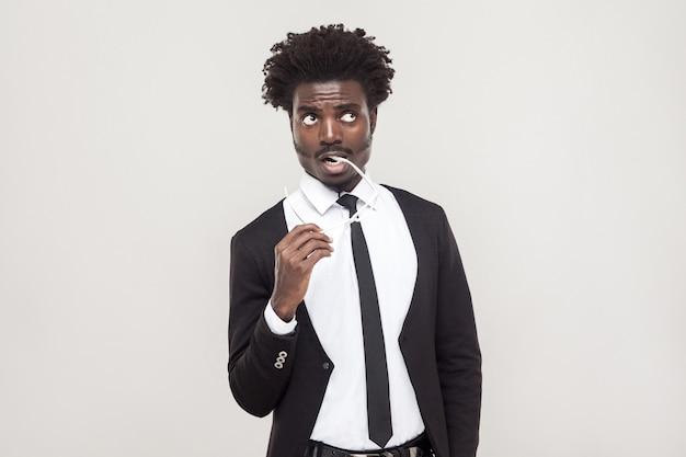 Denkende, erfreute leute. afrikanischer geschäftsmann, der nachdenkt und aufschaut. studioaufnahme, grauer hintergrund